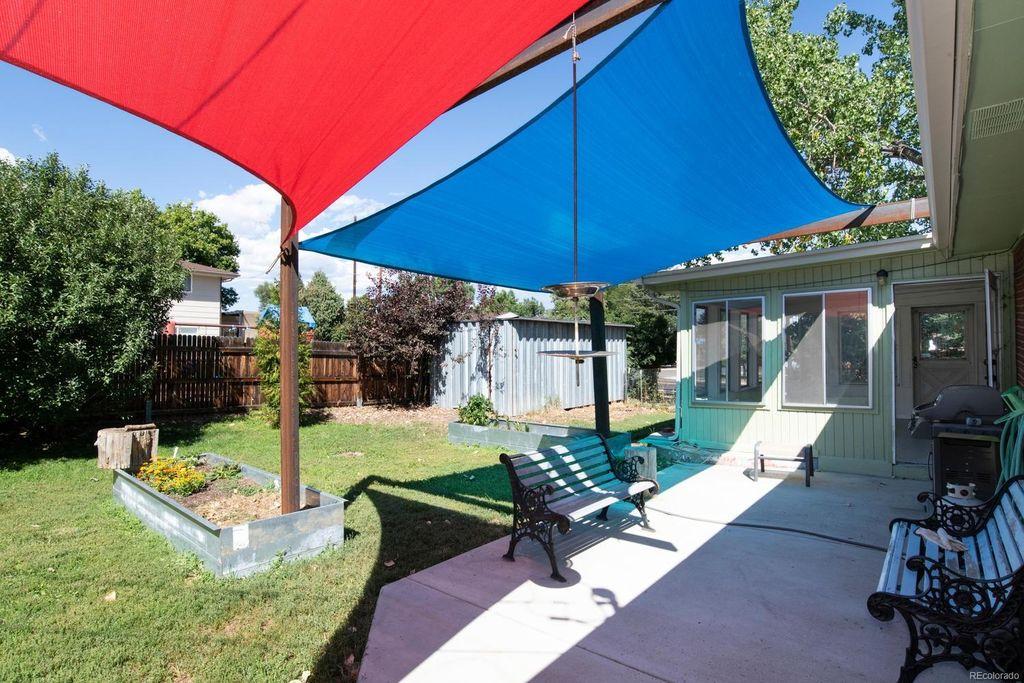 Original metal planter boxes attached to the house with shade sails.